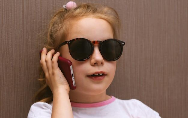 Menina criança em óculos de sol com smartphone