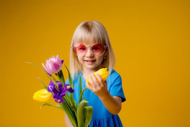 Menina criança em óculos de sol em roupas azuis, sorrindo e segurando um buquê de flores sobre fundo amarelo de isolar