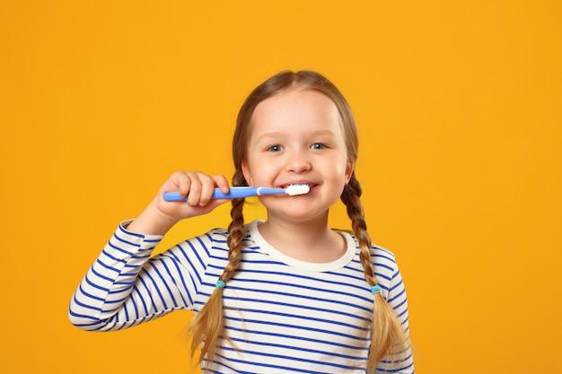 Menina criança em pijama listrado, escovando os dentes com uma escova de dentes