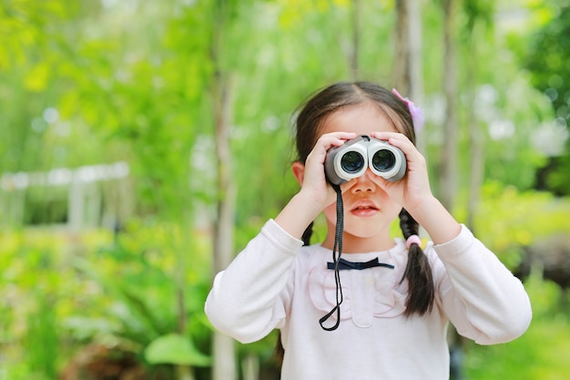 Menina criança em um campo, olhando através de binóculos na natureza ao ar livre