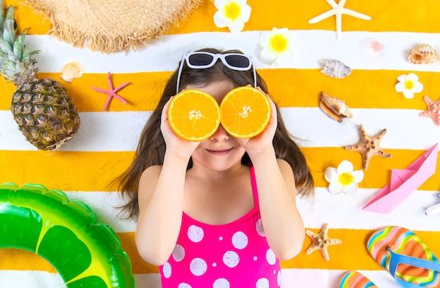 Menina criança em uma toalha de praia à beira-mar. foco seletivo. criança.