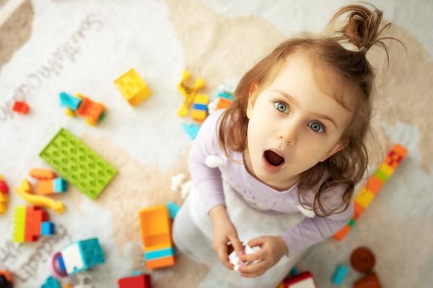Menina criança emocional surpresa com grandes olhos azuis sentada no chão da sala infantil e brincar com blocos coloridos