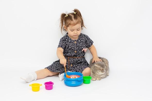 Menina criança engraçada alimentando um gatinho atraente