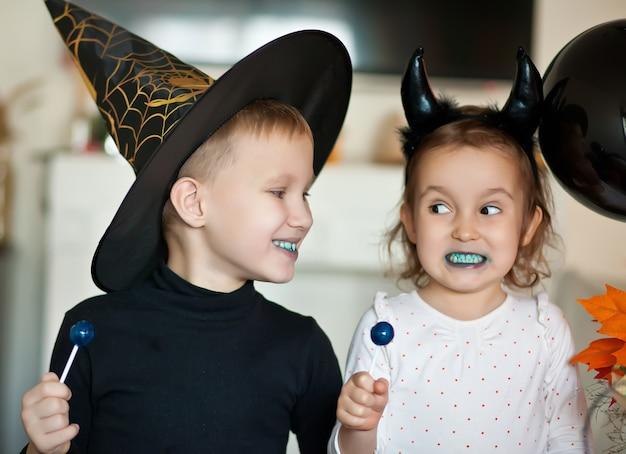 Menina criança engraçada e menino adolescente em fantasias de bruxa e mal para a festa de halloween comendo doces de pirulito e se divertir