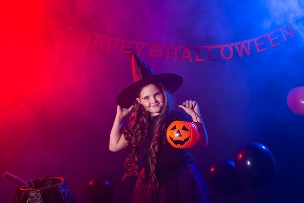 Menina criança engraçada fantasiada de bruxa para o halloween com a abóbora jack.