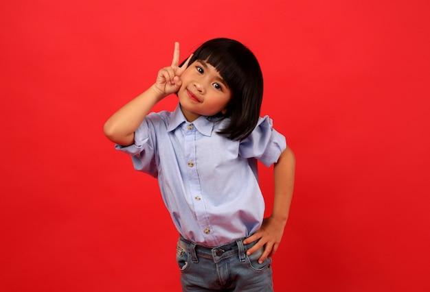 Menina criança está apontando o dedo no estúdio.