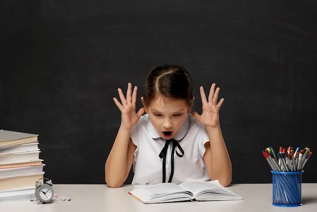 Menina criança estressada lendo um livro em sala de aula no fundo do quadro-negro. criança fazendo lição de casa