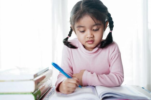 Menina criança estudante asiática escrevendo no livro de papel.
