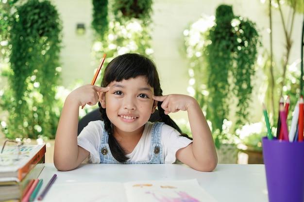 Menina criança estudante asiática fazendo lição de casa em casa.