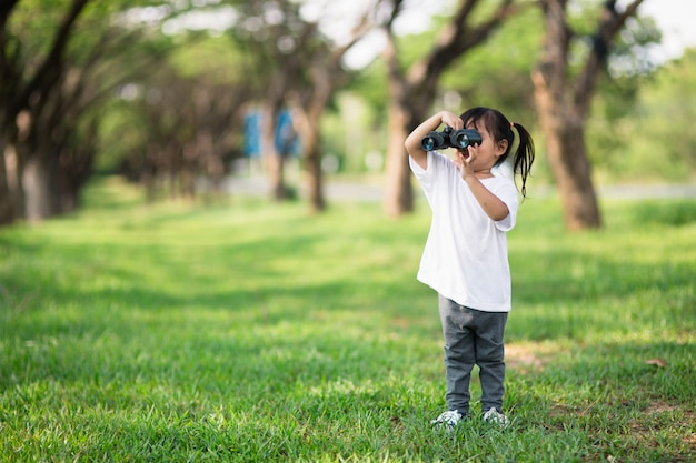 Menina criança feliz brincando com binóculos