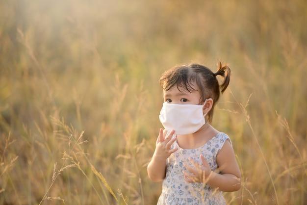 Menina criança feliz com máscara facial jogando no campo ensolarado, estilo de vida ao ar livre do verão, clima aconchegante
