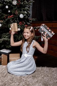 Menina criança feliz com presentes no chão da sala perto da árvore de natal.