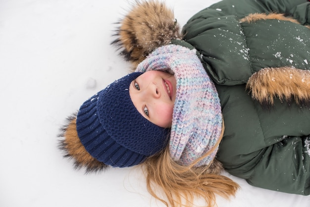 Menina criança feliz jogando neve em uma caminhada de inverno com neve
