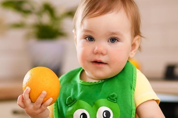 Menina criança feliz na cozinha come frutas saborosas, laranjas doces.