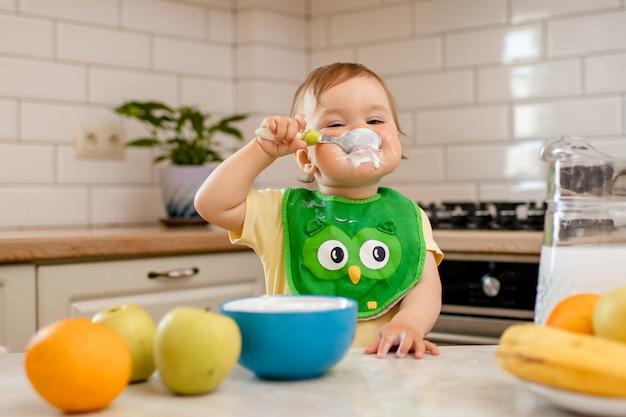 Menina criança feliz na cozinha come um delicioso queijo cottage e mingau.