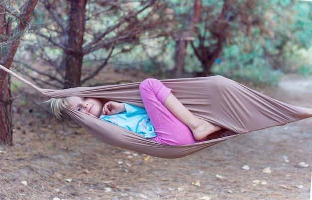 Menina criança feliz na rede na floresta de verão