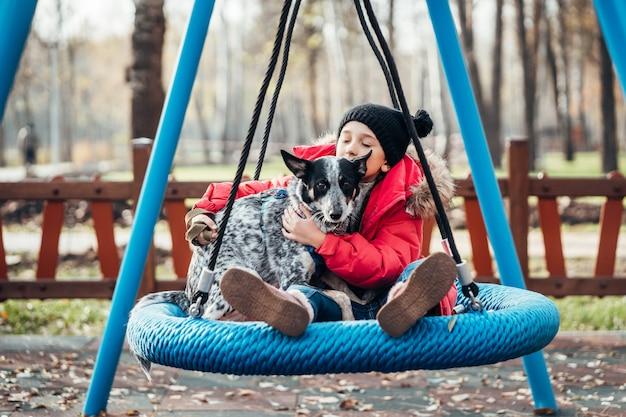 Menina criança feliz no balanço. menina em um balanço abraça seu cachorro.