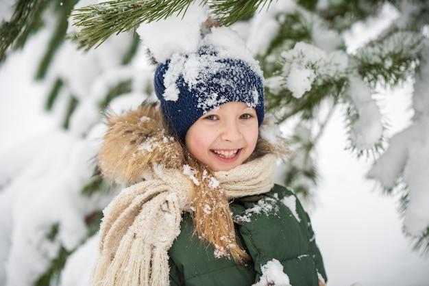 Menina criança feliz plaing com neve em uma caminhada de inverno nevado. uma criança em um bosque nevado. spruce galhos de árvores na neve.