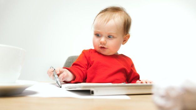 Menina criança feliz sentada com caneta e teclado de computador moderno ou laptop isolado em um estúdio branco.