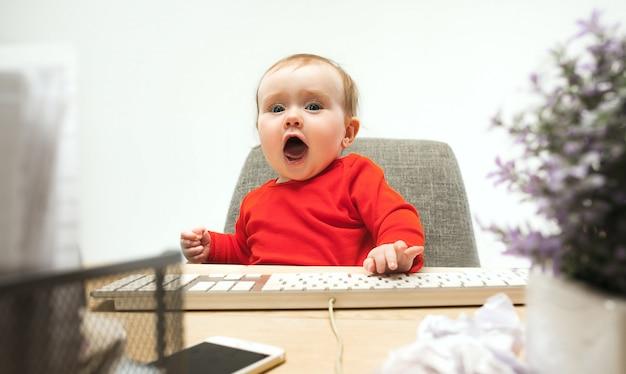Menina criança feliz, sentado com o teclado do computador moderno ou laptop isolado em um estúdio branco