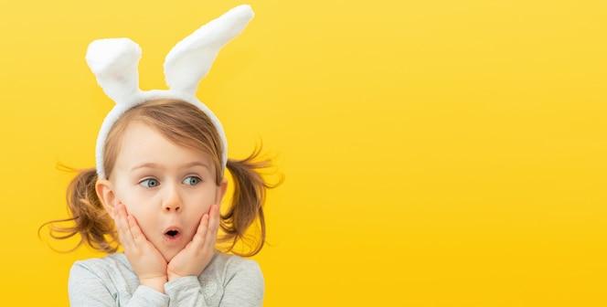 Menina criança fofa surpresa com orelhas de coelho em fundo amarelo no estúdio