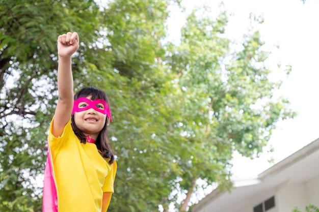 Menina criança joga super-herói. criança em fundo branco. conceito de poder feminino Foto Premium