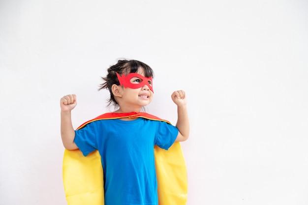 Menina criança joga super-herói. criança em fundo branco. conceito de poder feminino