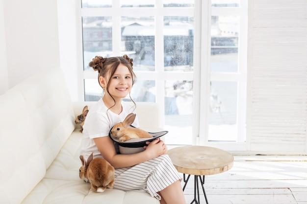 Menina criança linda e feliz sentada no sofá com animais coelho em um chapéu em casa