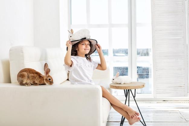 Menina criança linda e feliz sentada no sofá com um coelho de pequenos animais em um chapéu