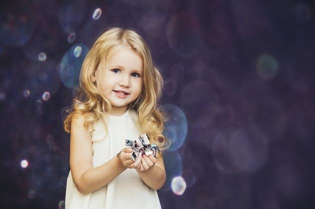 Menina criança linda e linda com o brilho do fundo feliz feliz com confete