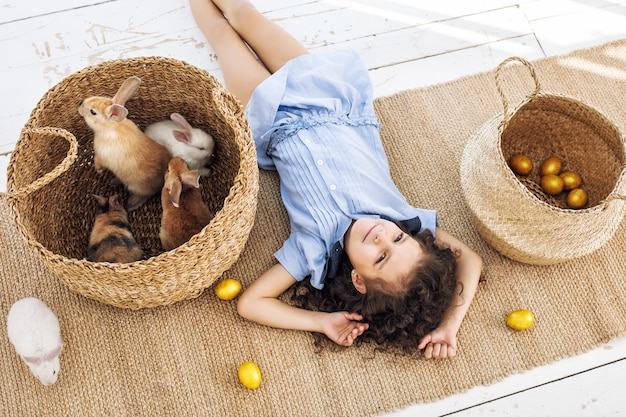 Menina criança linda fofa alegre e feliz com coelho de pequenos animais e ovos de páscoa em casa