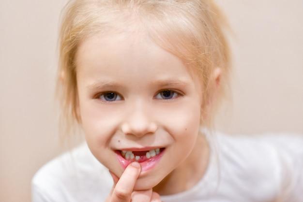 Menina criança mostra mudança de dente de leite