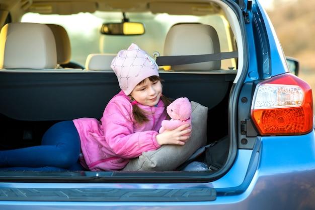 Menina criança muito feliz brincando com um ursinho de pelúcia de brinquedo rosa no porta-malas de um carro.