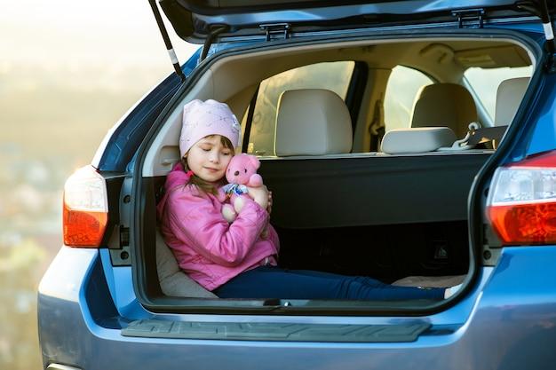 Menina criança muito feliz brincando com um ursinho de pelúcia de brinquedo rosa no porta-malas de um carro
