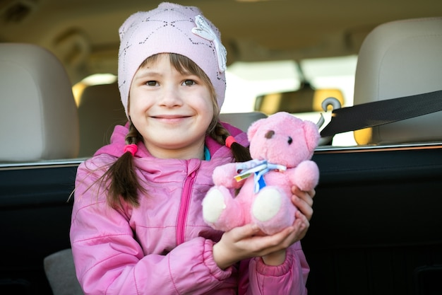 Menina criança muito feliz brincando com um ursinho de pelúcia de brinquedo rosa sentado no porta-malas de um carro.