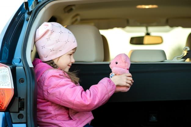 Menina criança muito feliz brincando com um urso de pelúcia rosa brinquedo em uma mala do carro.