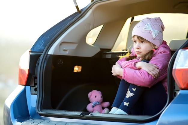 Menina criança muito triste sentada sozinha no porta-malas de um carro com um ursinho de pelúcia de brinquedo rosa.