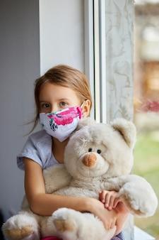 Menina, criança na máscara com ursinho de pelúcia senta-se nas janelas, quarentena de coronavírus