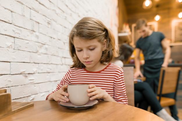 Menina criança no café com grande copo de arte bebida