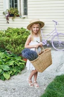 Menina criança no chapéu com uma cesta de lavanda no jardim no verão