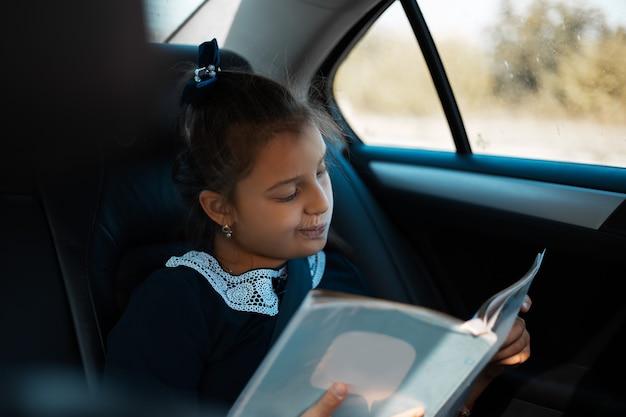 Menina criança olhando para o livro no carro, usando o formulário da escola. a caminho de casa depois da escola.