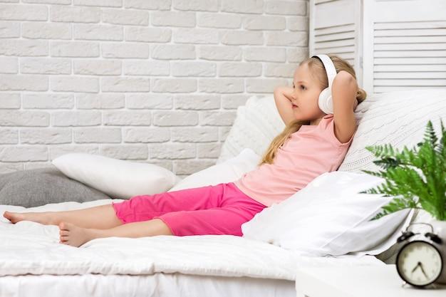 Menina criança ouvindo a música com os fones de ouvido