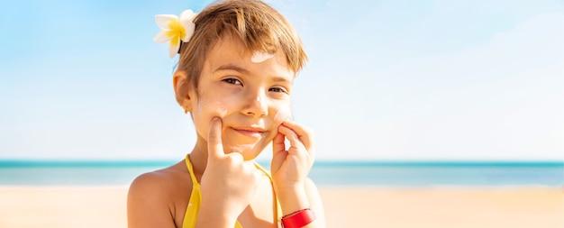 Menina criança passando protetor solar no rosto
