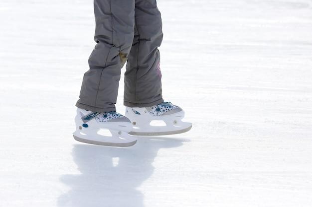 Menina criança patinando na pista de gelo