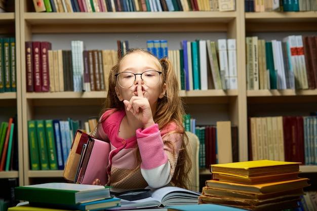 Menina criança pede para ficar quieta na biblioteca, criança em idade escolar senta-se sozinha à mesa com livros, segurando um dedo na boca, conceito de manter silêncio