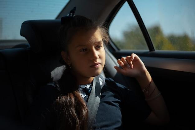 Menina criança pensativa em forma de escola, sentada no carro depois da escola.