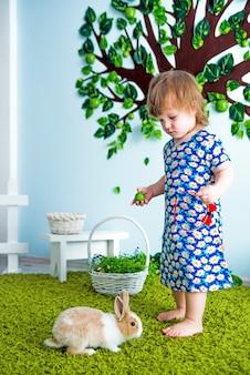 Menina criança pequena no vestido azul com coelho no tapete de grama perto de macieira