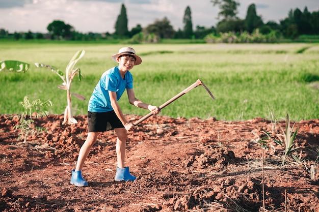 Menina criança segurando enxada e cavar solo para plantar árvores no jardim