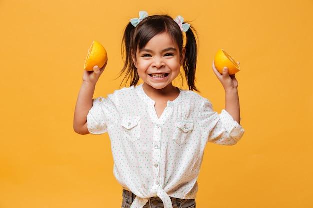 Menina criança segurando laranja.