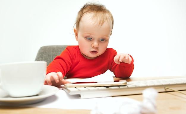 Menina criança sentada com teclado de computador moderno ou laptop em estúdio branco.